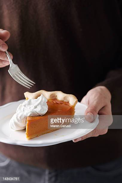 Man holding plated pumpkin pie slice and fork