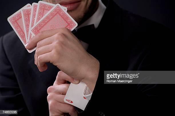 man holding playing cards, ace in sleeve - zaubertrick stock-fotos und bilder