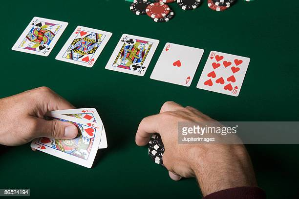 man holding playing cards and poker chips - texas hold 'em stock pictures, royalty-free photos & images