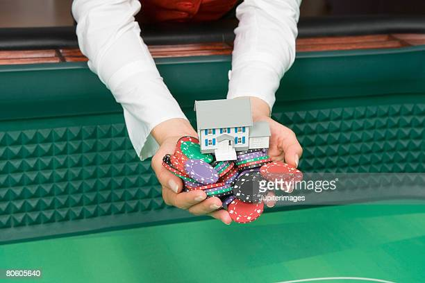 Man holding poker chips and toy house