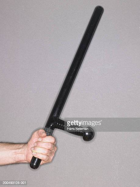 man holding police baton, side view - truncheon stock pictures, royalty-free photos & images