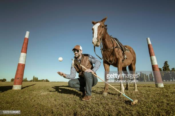 Man Holding Polo Mallet While Playing With Ball By Horse On Field