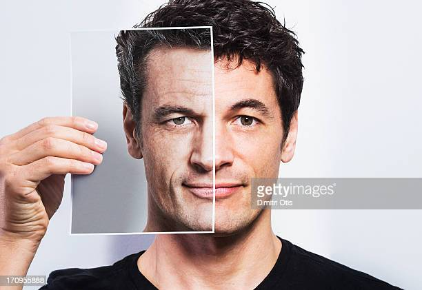 man holding portrait of older version of himself - retouched image stock photos and pictures