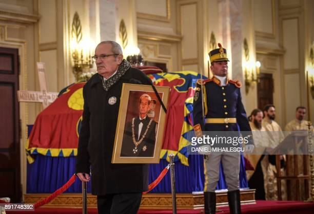 A man holding portrait of the late King Michael walks past the coffin of King Michael I of Romania on December 13 2017 at the former Royal Palace...