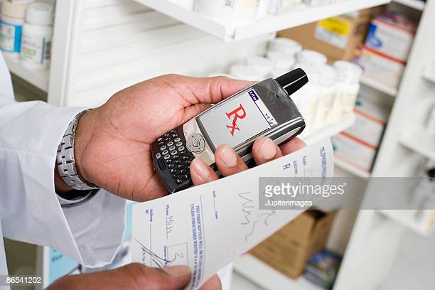 Man holding prescription and portable communication device