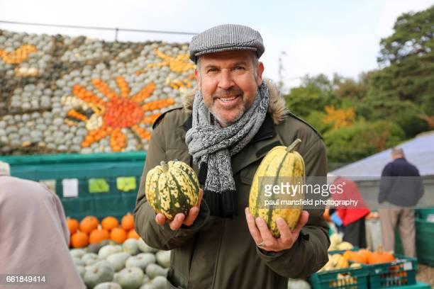 man holding pumpkins - flat cap stock photos and pictures
