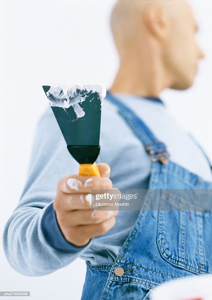 Man holding putty knife, low angle view : Stockfoto