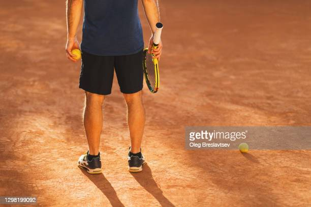 man holding racket and ball - tennis stock pictures, royalty-free photos & images