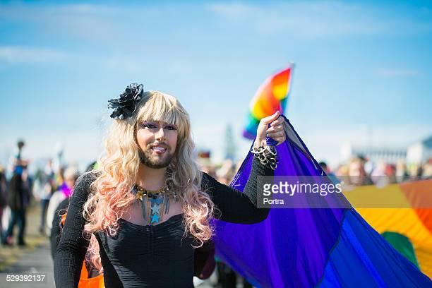 man holding rainbow flag during gay parade - crossdresser - fotografias e filmes do acervo