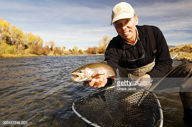 Man holding rainbow trout and fly-fishing net in river, portrait
