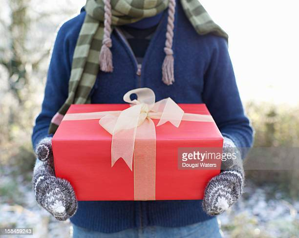 man holding red christmas present outside in snow. - holiday shopping stock photos and pictures