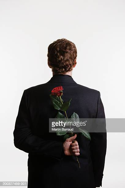 man holding red rose behind back - hands behind back stock pictures, royalty-free photos & images