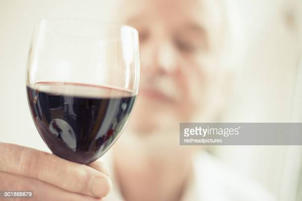 Man holding red wine, close up