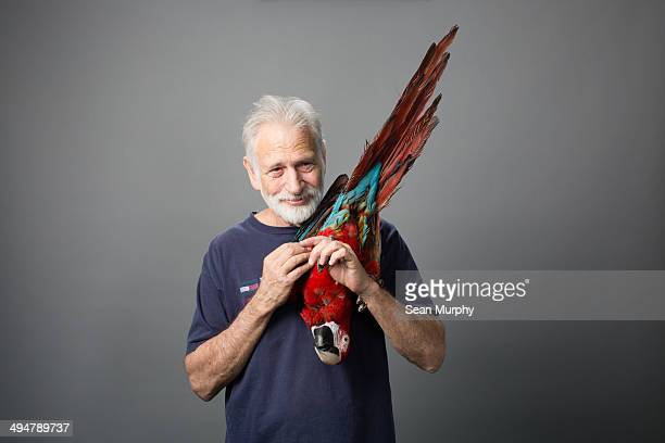 Man holding Red-and-green Macaw upside down