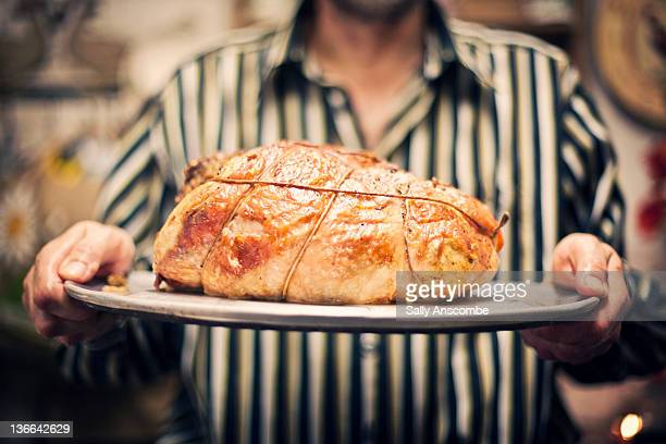 Man holding roast turkey