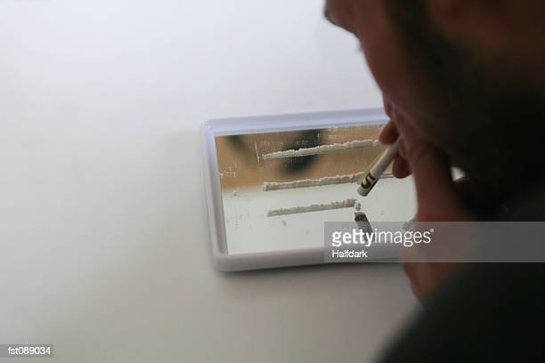 man holding rolled bank note over lines of cocaine - sniffare droga foto e immagini stock