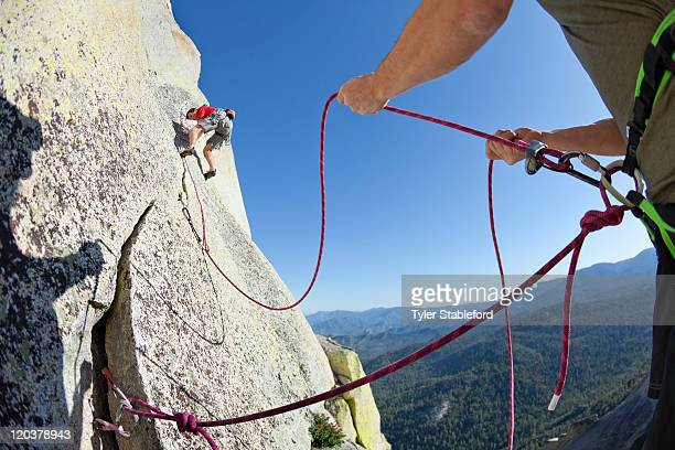 Man holding ropes and assising climber on rock.