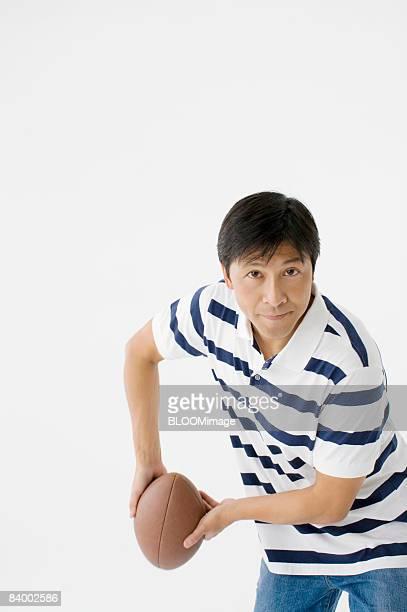 Man holding rugby ball, studio shot