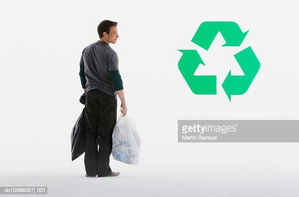 Man holding sacks of rubbish, standing next to recycle symbol, rear view