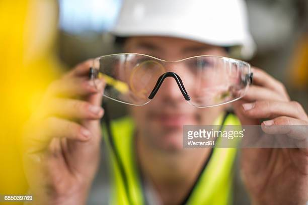 Man holding safety glasses