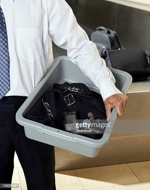 Man holding security x-ray tray at airport security, mid section