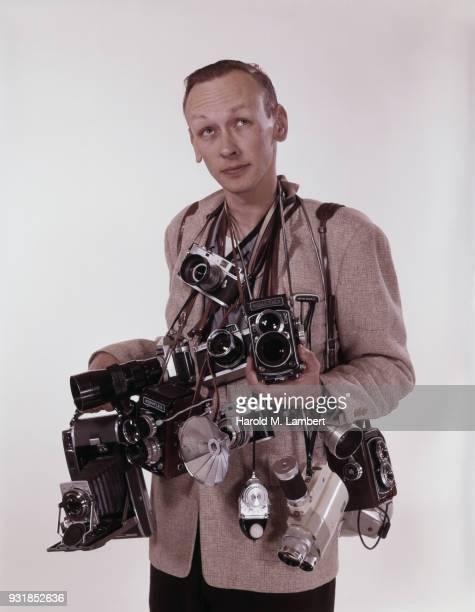 Man holding several cameras in studio