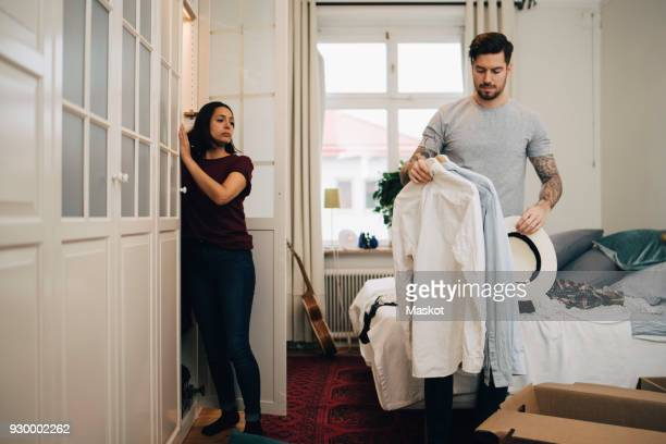 Man holding shirts and hat while standing by woman in new home