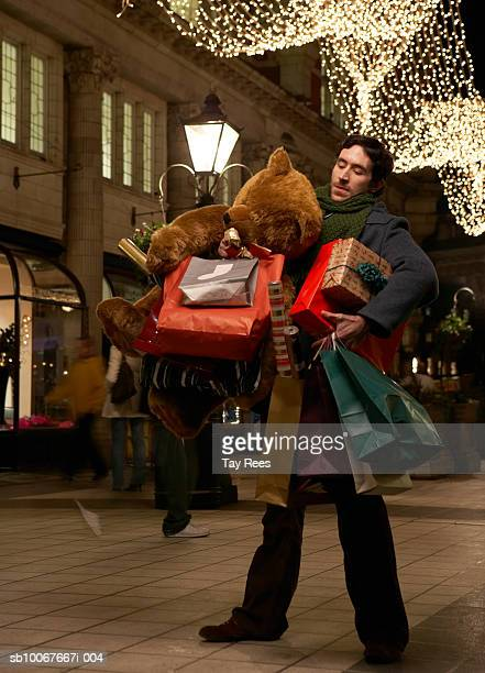 Man holding shopping bags and giant teddy bear, standing on street at night