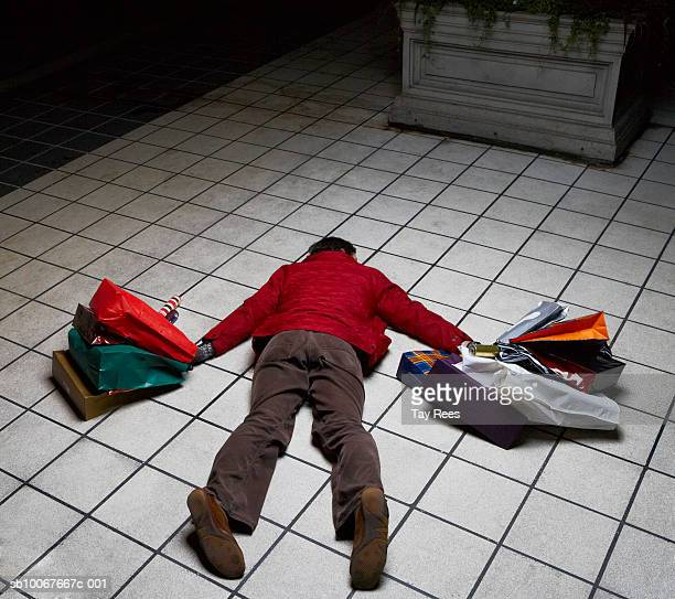 Man holding shopping bags lying face down on floor, rear view
