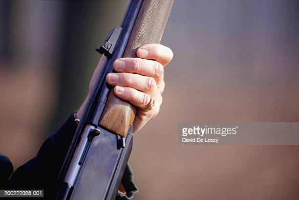 man holding shotgun, mid section, close-up of hand - shotgun stock pictures, royalty-free photos & images