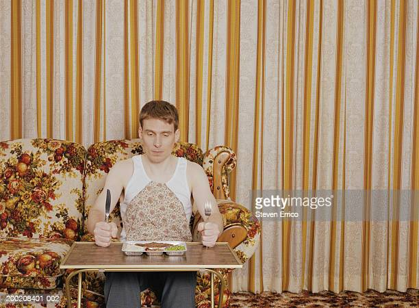 man holding silverware, sitting at serving tray with tv dinner - cibo pronto foto e immagini stock