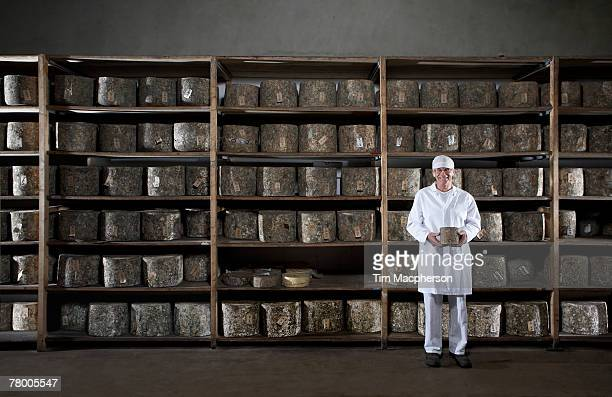 Man holding small cheese  in front of rack of cheeses.
