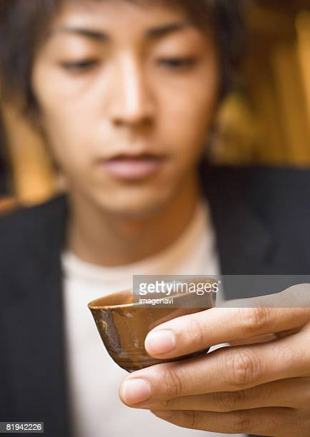 Man Holding Small Sake Cup