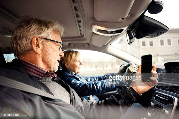 Man holding smart phone while sitting by senior woman driving car in city
