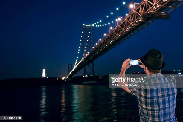 Man holding smartphone taking picture at the 25 Abril Bridge, Lisbon, Portugal.
