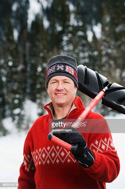 man holding snow shovel - snow shovel stock photos and pictures