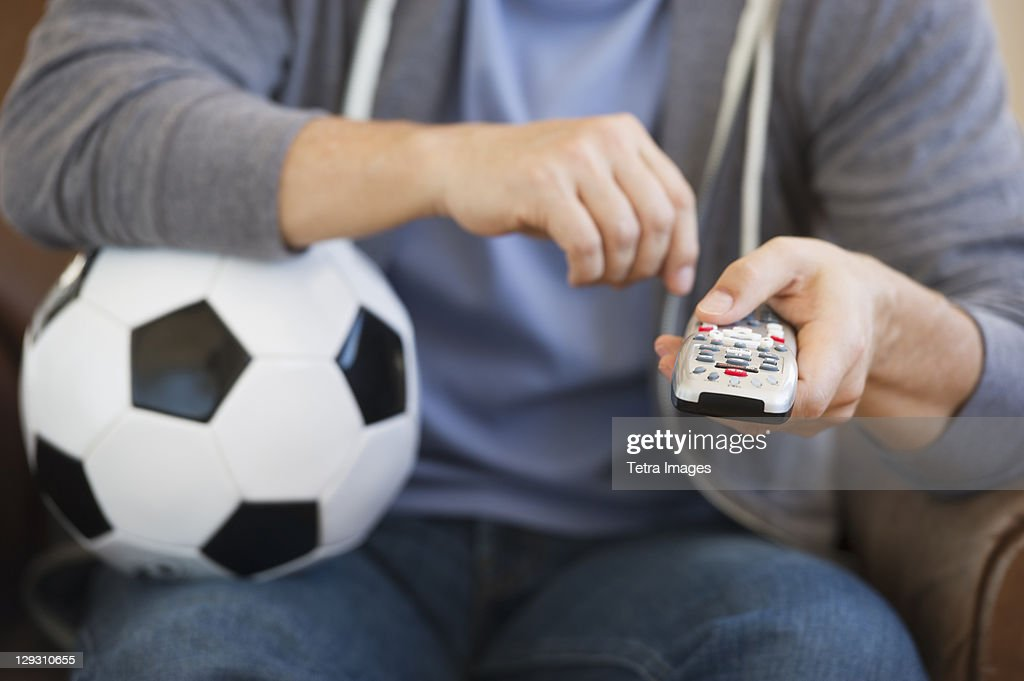 Man holding soccer ball and remote control : Stock-Foto