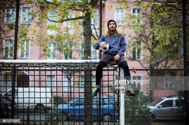 man holding soccer ball and sitting on post - goal post stock photos and pictures