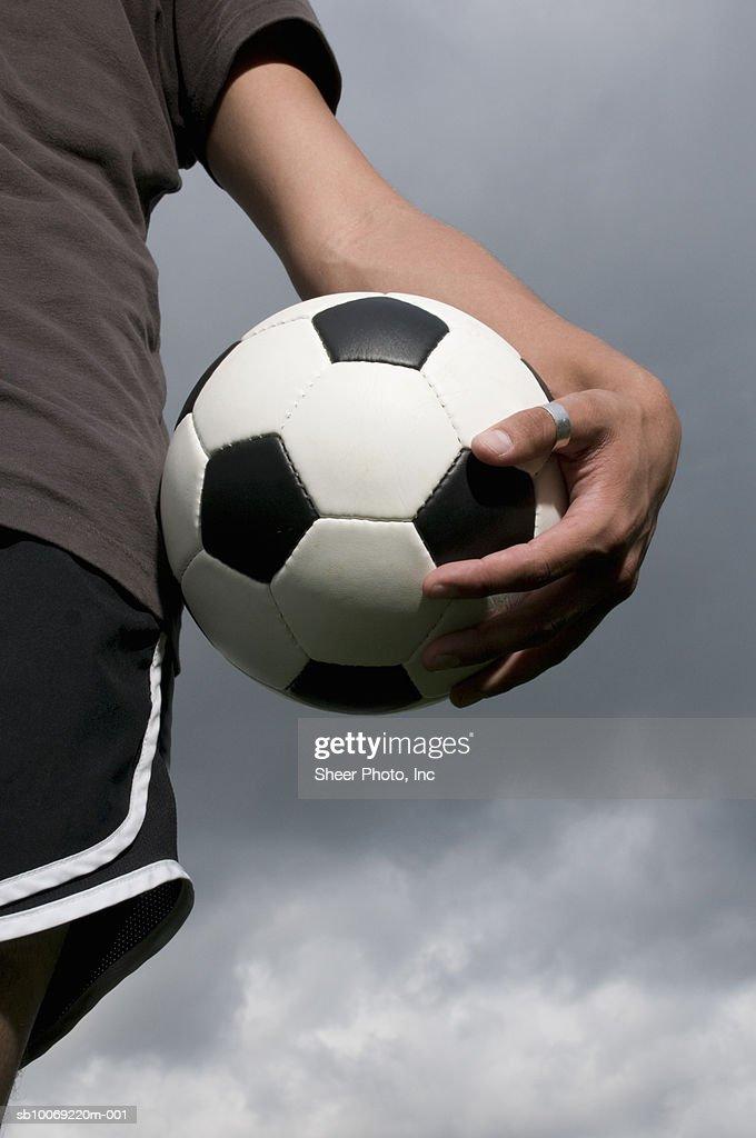Man holding soccer ball, mid section : Stockfoto