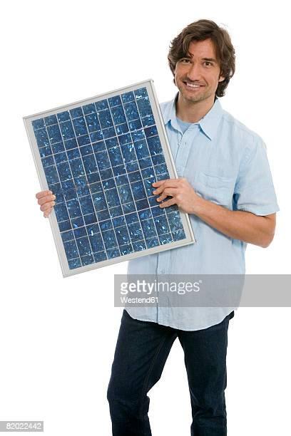 Man holding solar panel, smiling, portrait