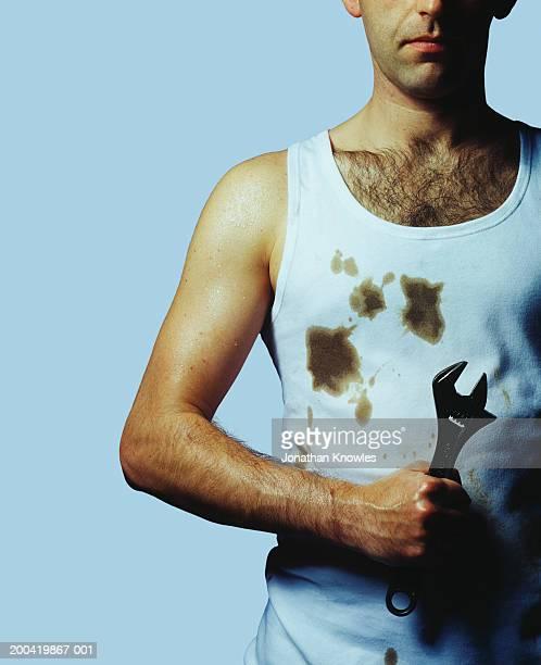 man holding spanner, mid section - hairy chest fotografías e imágenes de stock