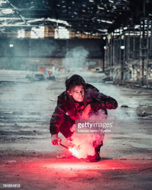 man holding sparkler while crouching in factory - 25 29歳 ストックフォトと画像