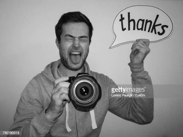 Man Holding Speech Bubble With Thanks Text While Photographing By White Background