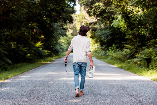 Man holding sports shoes and sunglasses while walking on road amidst trees