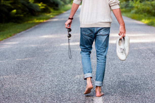 Man holding sports shoes and sunglasses while walking on road in forest