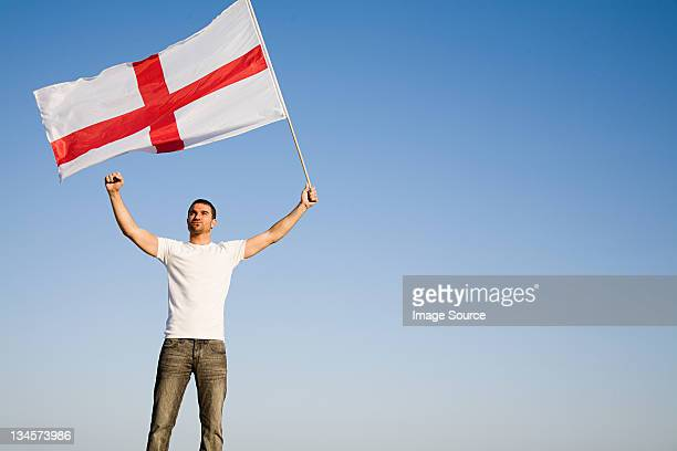 man holding st george's cross flag in the air - bandiera inglese foto e immagini stock