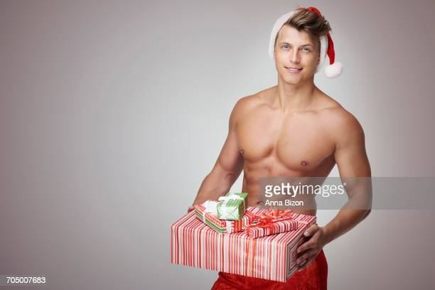 Man holding stack of Christmas presents. Debica, Poland