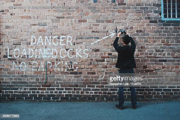 Man Holding Sunglasses In Front Of Brick Wall