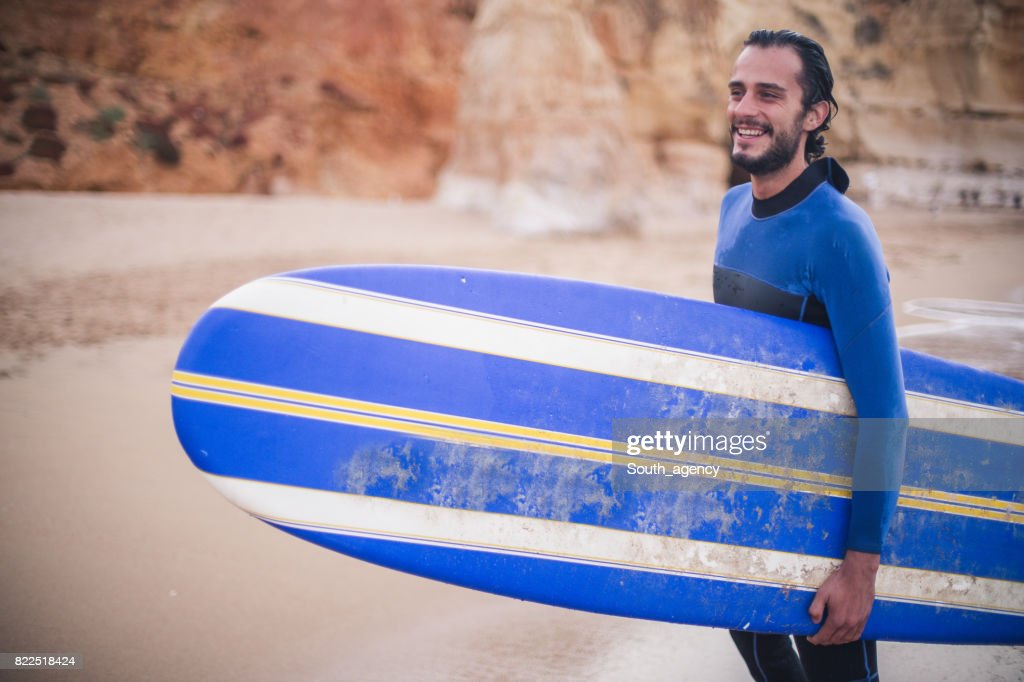 Man holding surfboard at the beach : Stock Photo