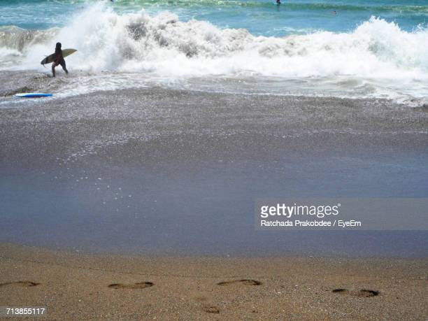 Man Holding Surfboard By Waves In Sea On Shore At Beach
